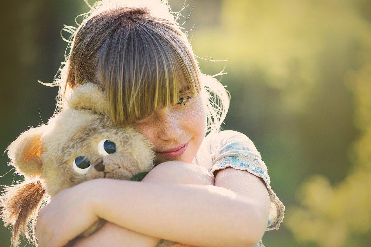 petite fille qui caline son ours en peluche