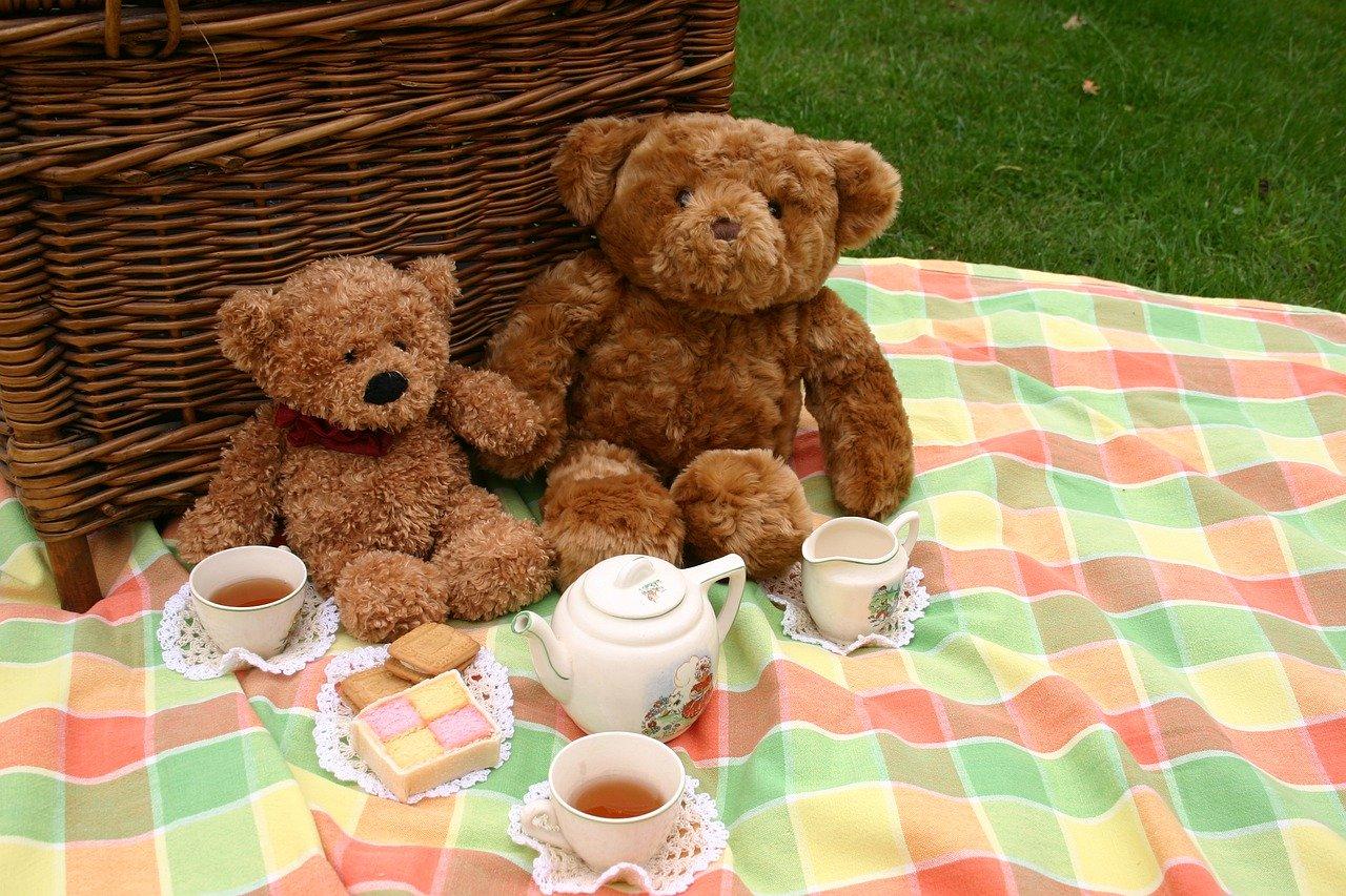 peluches oursons qui prennent le thé sur une nappe de pique-nique avec un panier en osier